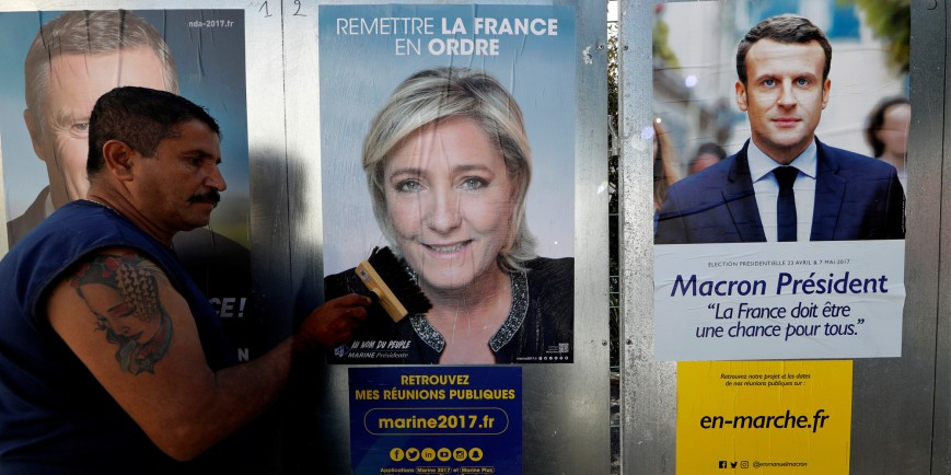 Sauveur, a member of the French National Front (FN) political party pastes a poster on a official billboard for French National Front (FN) political party leader Marine Le Pen as part of the 2017 French presidential election campaign in Antibes